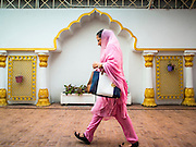 "08 FEBRUARY 2015  BANGKOK, THAILAND: A woman walks in the Sikh temple in Bangkok. Thailand has a small but influential Sikh community. Sikhs started coming to Thailand, then Siam, in the 1890s. There are now several thousand Thai-Indian Sikh families. The Sikh temple in Bangkok, Gurdwara Siri Guru Singh Sabha, was established in 1913. The current building, adjacent to the original Gurdwara (""Gateway to the Guru""), was built in 1979. The Sikh community serves a daily free vegetarian meal at the Gurdwara that is available to people of any faith and background.     PHOTO BY JACK KURTZ"