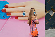 A lady using her mobile phone and with painted nails passes a temporary construction hoarding for the jewellery retailer Hirsch that features a manicured hand, painted nails and an unheated Paraíba Tourmaline ring, set with fine white diamonds designed by HIRSH, on 13th August 2019, in London England.