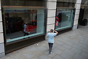 A man walks looking at his own reflection in the window of a car showroom dealership on Piccadilly in central London, on 24th September, in London, England.