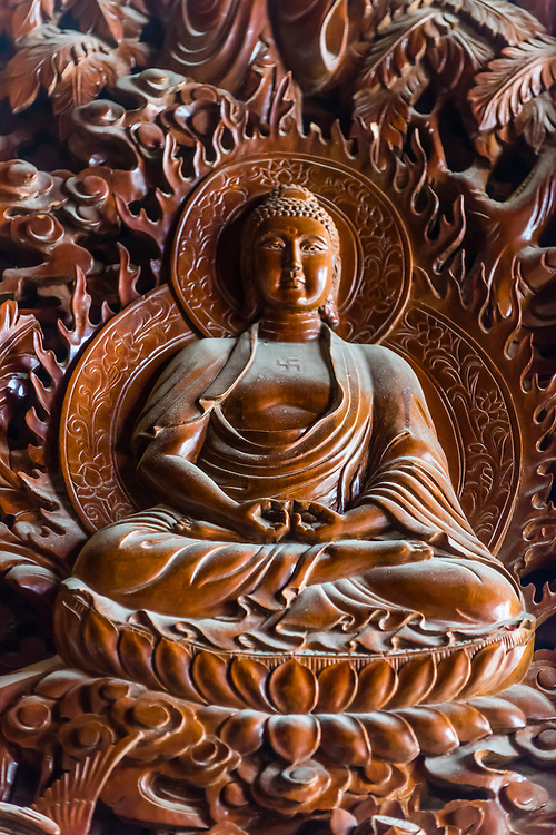 Ornate detailed carvings, including this one of Buddha, on massive teak doors, Chongsheng Temple, Dali, Yunnan Province, China. The temple dates from the 9th and 10th centuries.