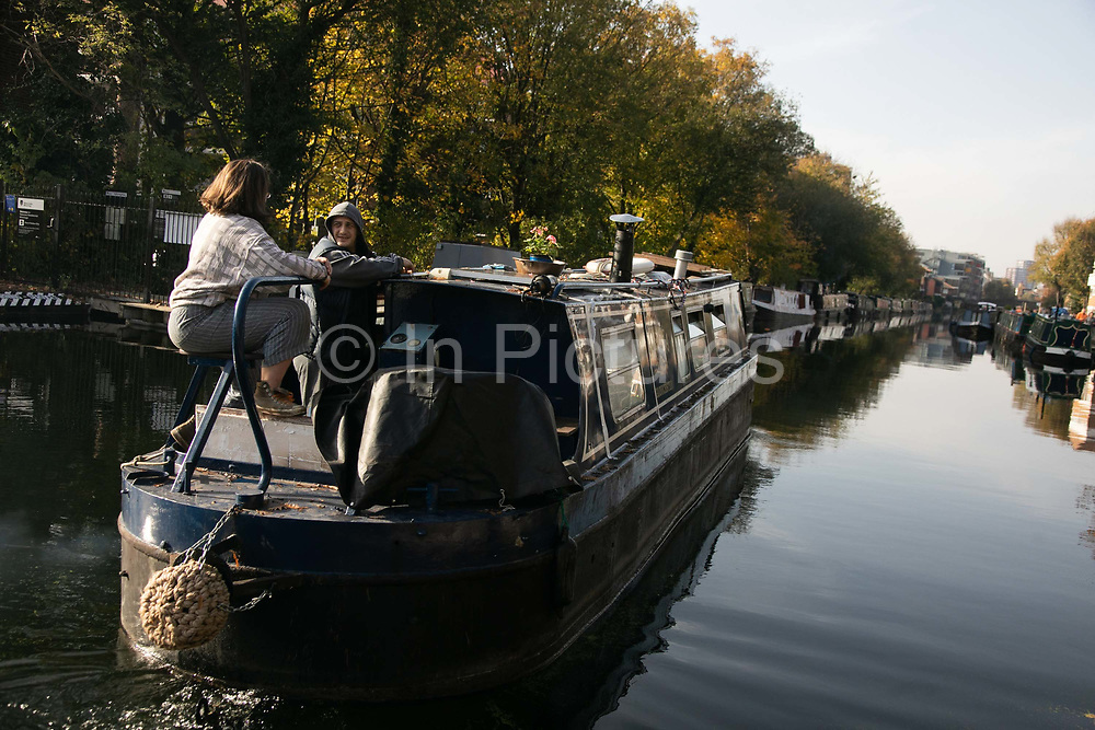 A canal boat cruises down the Regents Canal in Hackney during the second coronavirus national lockdownon on 7th of November 2020, East London, United Kingdom. The canal is home to many living in boats and the canal has become both a home to many and a place to spend time on a sunny day. <br /> The lockdown restrictions mean that people are only allowed to meet outside, in pairs and only if keeping social distance.