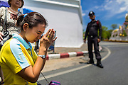 05 MAY 2013 - BANGKOK, THAILAND: A woman prays in the street after waiting to see Bhumibol Adulyadej, the King of Thailand, in his royal motorcade Sunday. The King and Queen, who are both hospitalized and in poor health, did not attend Sunday's event. May 5 marks the 63rd anniversary of the Coronation of His Majesty King Bhumibol Adulyadej. The day is celebrated as a national holiday; since this year it falls on a Sunday, it will be observed on Monday May 6, and as such all government offices and commercial banks will close for the day. HM King Bhumibol Adulyadej is the longest reigning monarch in the world. Each year on the 5th of May, the Kingdom of Thailand commemorates the day when, in 1950, the Coronation Ceremony was held for His Majesty King Bhumibol Adulyadej, the 9th in the Chakri Dynasty (Rama IX). On the 5th of May, His Majesty conducts a merit making ceremony, presenting offerings to Buddhist monks, and leads a ?Wien Thien? ceremony, walking three times around sacred grounds at the Temple of the Emerald Buddha. PHOTO BY JACK KURTZ