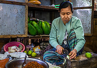 BAGAN, MYANMAR - CIRCA DECEMBER 2013: Woman cutting vegetables in the Nyaung U market close to Bagan in Myanmar