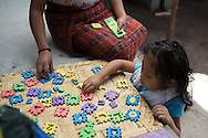 Silva and Gladys play a game with numbers and letters. In a year, Gladys will learn how to make clothing like the other female members of her family. This will most likely be what she does to support her family when she becomes an adult.
