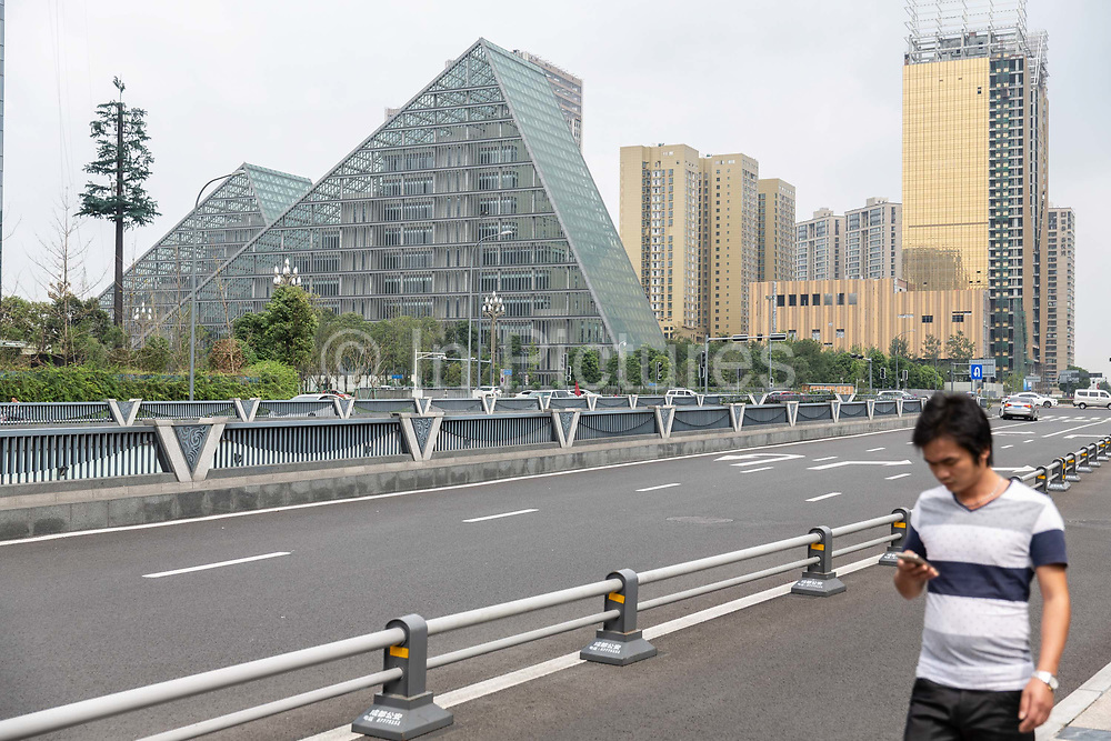 A pedestrian walks through the central business district of Chengdu, China, on Monday, Sept. 19, 2016. China faces unprecedented challenges as it restructures its economy away from old-line heavy manufacturing and toward consumption and services.