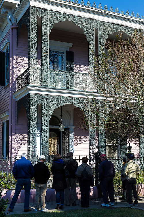 Tour group at grand mansion house, ornate wrought iron fretwork gallery, the Garden District, New Orleans, Louisiana USA
