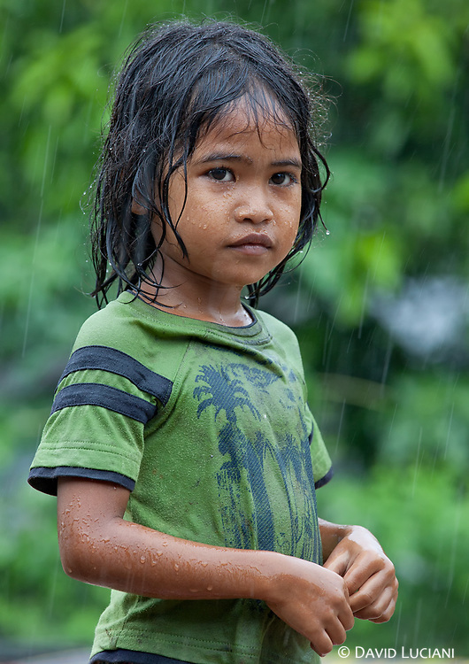 Girl standing under heavy rain along the bamboo train railway.