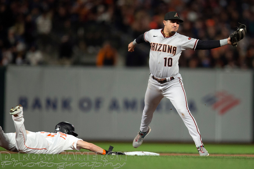Arizona Diamondbacks shortstop Josh Rojas (10) fields a pickoff throw as San Francisco Giants' Mike Yastrzemski (5) slides safely back into second base during the fourth inning of a baseball game, Tuesday, Sept. 28, 2021, in San Francisco. (AP Photo/D. Ross Cameron)