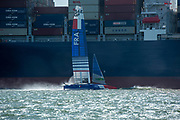 SailGP Team France helmed by Billy pass a container ship as they return to the technical area after practice. Event 4 Season 1 SailGP event in Cowes, Isle of Wight, England, United Kingdom. 5 August 2019: Photo Chris Cameron for SailGP. Handout image supplied by SailGP