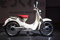 """Honda unveils the new electric cub, a repro of its old timer """"Cub"""" one of the most popular and widely sold motor scooters in the world.  This one, however, is electric.  Tokyo Motor Show is a biennial auto show held in October or November at the Makuhari Messe event space in Japan for cars, motorcycles and commercial vehicles. Hosted by the Japan Automobile Manufacturers Association (JAMA)  it is a recognized international show by the Organisation Internationale des Constructeurs d'Automobiles, and normally sees more concept cars than actual production car introductions. The press see the show as one of the big five along with Detroit, Geneva, Frankfurt and Paris.   In 2009 new hybrids and electric vehicles from Japan's leading automakers dominate the show. Toyota Motor Corporation introduced its 1/X concept vehicle, a Prius-like sedan that has a third of the weight of the Prius and obtains double the Prius' fuel economy. The vehicle cuts its weight by using carbon fiber reinforced plastic in its frame and boosts fuel economy with a small plug-in hybrid powertrain that can be fueled with either gasoline a blend of 85% ethanol and 15% gasoline. Toyota's other plug-in hybrid concept, the Hi-CT, is a small, boxy, two-door vehicle aimed at the youth market.   Among the other automakers, Honda Motor Company, Ltd., unveiled the CR-Z, a """"next-generation lightweight sports car"""" that features Honda's hybrid electric drivetrain, and the PUYO, another small, boxy vehicle, powered by a fuel cell. Honda will also unveil the one-wheeled scooter transport, the Honda U3-X.  While Nissan unveiled the Pivo 2, a small electric vehicle with a lithium-ion battery pack and wheel motors.."""