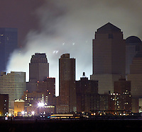 13 September 2001: View of smoke smoldering ashes burning in the rain only two days after the Terrorist attack on the America's. View of  Lower Manhattan, NY from Hoboken NJ. Area surrounding ground zero where the World Trade Centers WTC once stood only hours after they fell to the ground in New York.  Islamic terrorist Osama bin Laden declares The Jihad or Holy War against The United States of America on September 11, 2001. Headline news photos available for editorial use.
