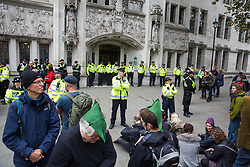 London, UK. 17 October, 2019. Metropolitan Police officers form a cordon in front of activists from the XR Peace group of Extinction Rebellion protesting outside the Supreme Court to highlight the Government's continuing failure to respect international law regarding arms sales as part of the 11th day of International Rebellion Autumn Uprising protests. Eight activists from the Trident Ploughshares group, including a 91-year-old man, glued themselves together outside the court.