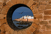 The walled city seen through a spy hole in the harbour wall. The Port of Essaouira lies on a strategic point of the Moroccan coastline. Its harbour is the scene of constant activity with fishing boats in dry dock, fishermen mending their nets and selling their catches at dawn. It is a UNESCO world heritage site.