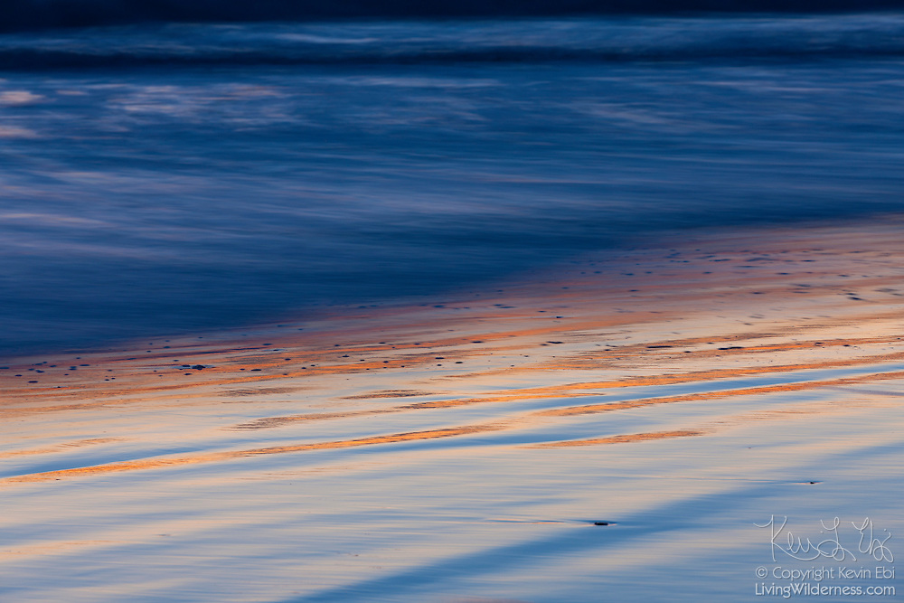A long camera exposure captures the movement of several small waves at twilight off Damon Point at Ocean Shores, Washington.