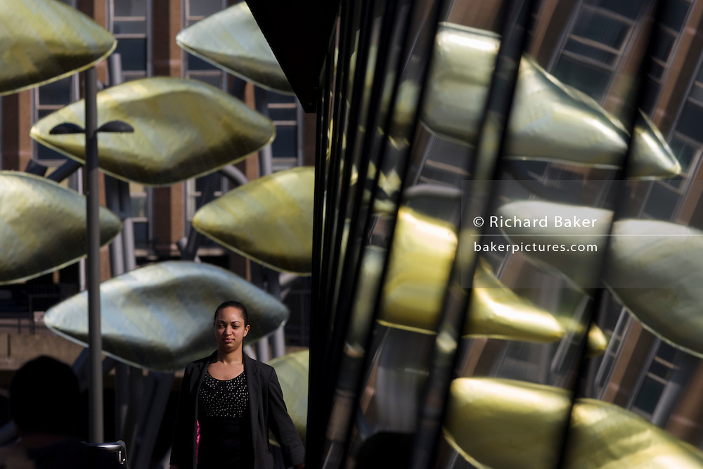 Young woman of mixed race on walkway with the new Olympic kinetic artwork called the Shoal at Stratford. 'The Shoal' at the Stratford Centre, east London, is made up of around 100 titanium clad 'leaves' mounted between 15 and 19 metres high on metal posts. Worth £13.5m, the Shoal is part of The Stratford Town Centre Public Realm Project, designed and manufacturered using 3D technology.
