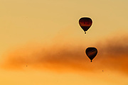 Two hot air balloons rise into the golden sky at sunset near Monroe, Washington.