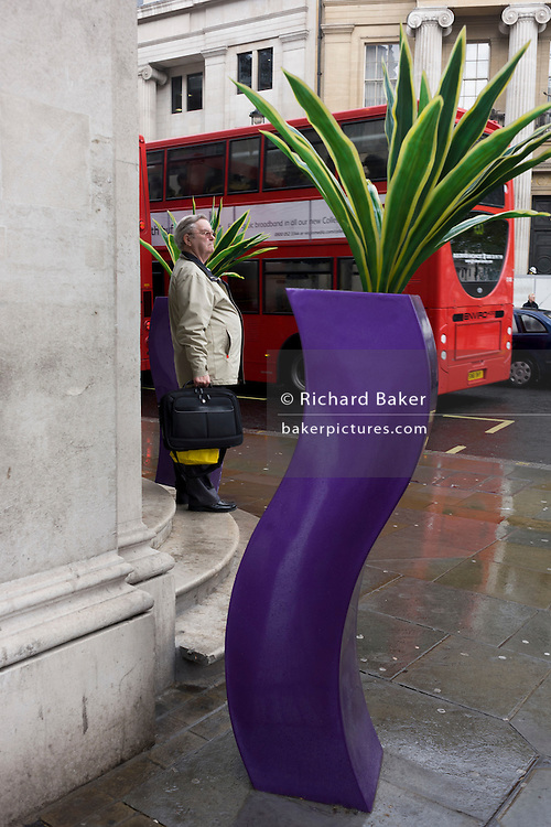 Large-bellied man stands alongside the curves of a pseudo-artistic plant stand feature in central London.