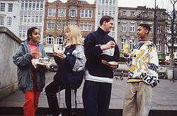 Multiracial group of teenagers standing in city centre eating junk food,