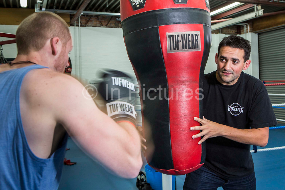 Two men boxing training also known as sparring using a heavy bag in the gym of Empire Fighting chance. Bristol, UK
