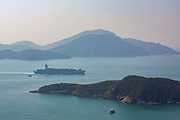 A large cargo ship crossing the Aberdeen Channel in Hong Kong on a hazy day. To the left is Oceans Park, and the island in the background is Lamma Island.