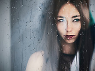 Pretty woman behind wet glass