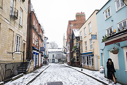 Windsor, UK. 24th January, 2021. A woman walks her dog after the first snowfall of winter. The current spell of cold weather is expected to continue for another two or three days.
