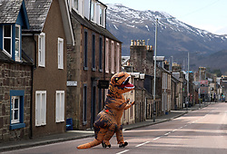 A person in a dinosaur costume runs along the main street in Callander, Perthshire as the UK continues in lockdown to help curb the spread of the coronavirus.
