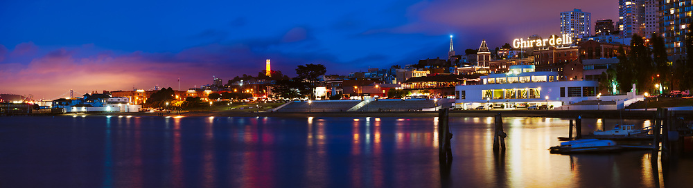 Aquatic Park is seen at blue hour, just after sundown from one of the pedestrian piers. The Transamerica pyramid is adorned with its winter light, and Coit tower glows orange for the San Francisco Giants. San Francisco, CA.