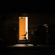 A townie sits in the open door light of a garage.
