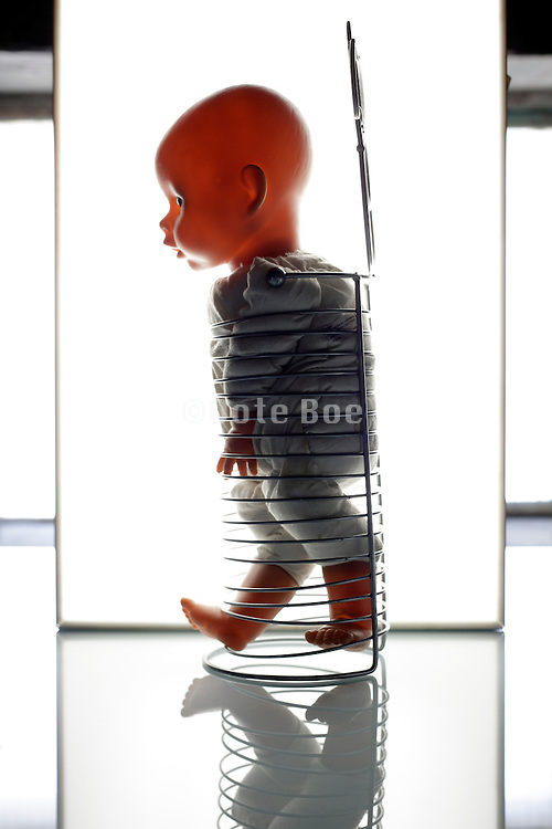 doll confined in metal coil