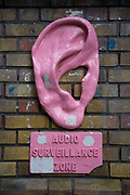 Audio Surveillance Zone street art near Brick Lane in the East End of London. This is an ever changing visual enigma, as the artworks constantly change, as councils clean some walls or new works go up in place of others. While some consider this vandalism or graffiti, these artworks are very popular among local people and visitors alike, as a sense of poignancy remains in the work, many of which have subtle messages.