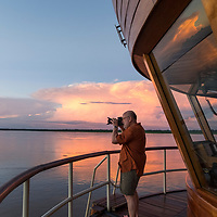 A Lindblad Expeditions guest photographs the sunset from the bow of the Delfin II ship on the Marañon River. Pacaya Samiria National Reserve, Upper Amazon, Peru.