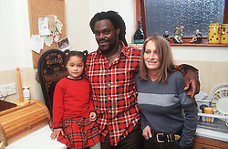 Multiracial family group standing together in kitchen smiling,