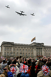 29 April 2011. London, England..Royal wedding day. A military fly past over Buckingham Palace as the Royal family watches from the balcony with cheering crowds below..Photo; Charlie Varley..