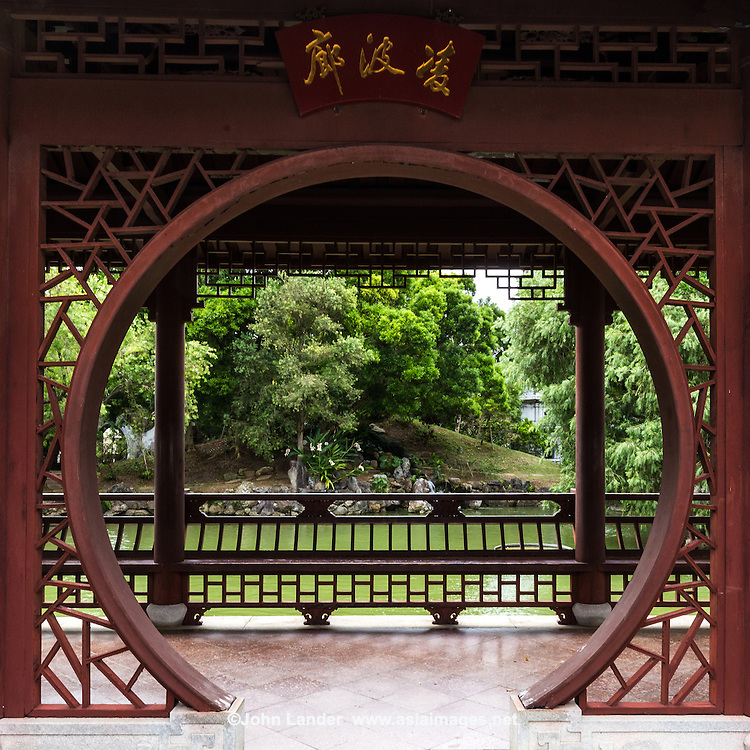 Moon Window at Fukushuen -  a traditional Chinese garden in Naha, Okinawa constructed in celebration of the 10th anniversary of the establishment of the sister city relationship between Naha and Fuzhou, China. Kume Naha, where the garden is located, was for centuries the center of Chinese culture in the Ryukyu Kingdom, and a symbol of the significant role of Chinese cultural influence in Okinawan culture and history.  The garden was built with the use of wood and stone from Fuzhou, with the help of artisans from Fuzho and therefore contains many of the elements of a traditional Chinese garden.  Several bridges extend over the pond, with koi carp and turtles: symbols of longevity and wisdom. The centerpiece of the garden is its waterfall, - the stones it flows from lead to a Chinese pavilion, allowing a view of the garden and surrounding scenery.  The Japanese concept of borrowed scenery shakkei is used, as well as local Okinawan elements of plants and trees chosen for the garden