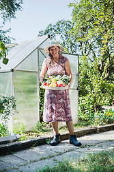 Senior woman with a basket of harvested vegetables in a garden, Altoetting, Bavaria, Germany