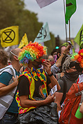 Protestors wearing a variety of clown and circus faces, dance, sing and cheer as they attend 'Carnival of Corruption' and march through Pall Mall street towards Trafalgar Square during an Extinction Rebellion climate change protest in London, Thursday, Sept. 3, 2020. The environmental nonviolent campaign group Extinction Rebellion plans to hold 10 days of demonstrations across central London as part of its ongoing campaign to highlight climate change. Peaceful actions swarmed central London into a standoff, demanding that the central government obeys and delivers Climate and Ecological Emergency Bill and prepare for crisis with a National Citizens' Assembly. (VXP Photo/ Vudi Xhymshiti)