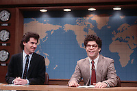 ca. 1986 --- Dennis Miller (left) and Al Franken (right) perform a Weekend Update skit on NBC's Saturday Night Live. --- Image by © Owen Franken/Corbis