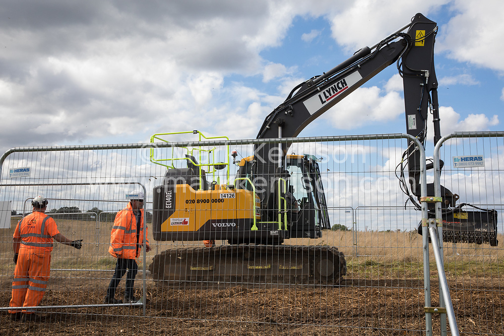 HS2 workers move a Volvo EC140E crawler excavator after anti-HS2 activists occupied mature oak trees and a trailer transporting wood chip in order to try to prevent or delay tree felling alongside the Fosse Way in connection with the HS2 high-speed rail link on 24th August 2020 in Offchurch, United Kingdom. The controversial HS2 infrastructure project is currently expected to cost £106bn and will destroy or significantly impact many irreplaceable natural habitats, including 108 ancient woodlands.