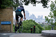 With the skyscrapers of the City of London, the capitals financial district, in the distance, a cyclist in morning rush-hour traffic, turnturns down Sydenham Hill, on 15th June 2021, in south London, England.