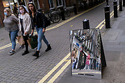 """Women shoppers walk along Neal Street, passing-by a mirrored sign for fashion retailer 'Subdued', on 12th July 2021, in London, England. 'Subdued' is an Italian brand """".. for fun-loving, strong and independent teenagers"""". Founded in the 90's they have 130 stores around the world."""
