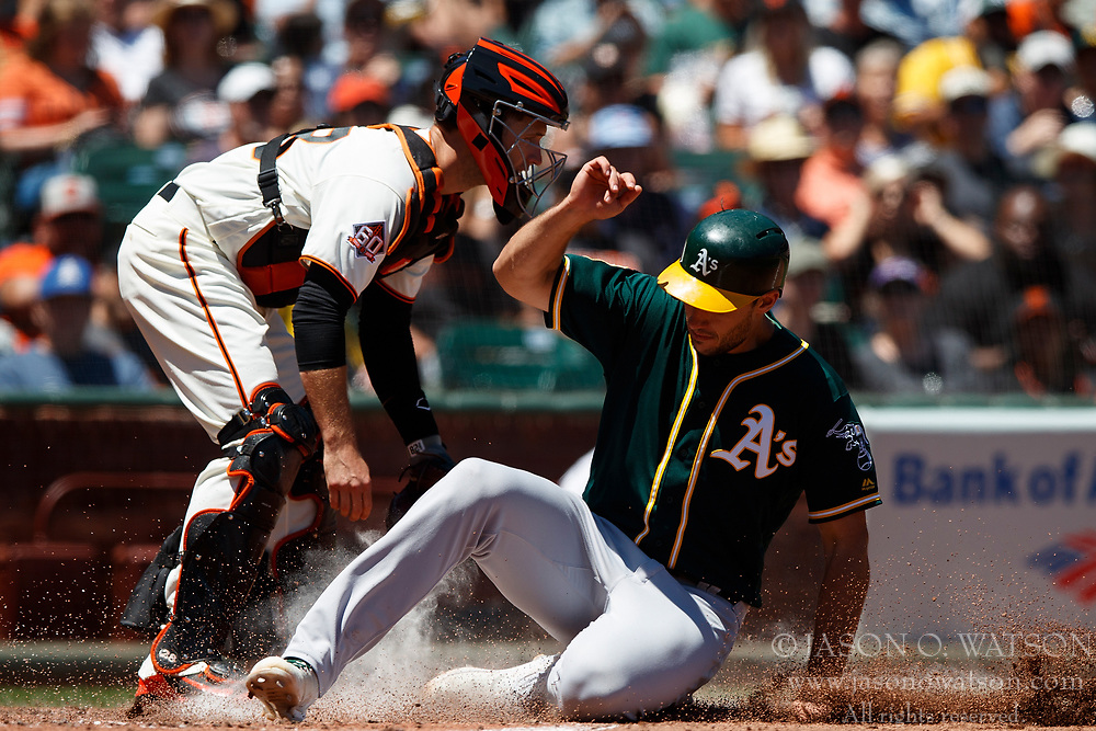 SAN FRANCISCO, CA - JULY 15: Stephen Piscotty #25 of the Oakland Athletics slides into home plate to score a run past Buster Posey #28 of the San Francisco Giants during the fourth inning at AT&T Park on July 15, 2018 in San Francisco, California. The Oakland Athletics defeated the San Francisco Giants 6-2. (Photo by Jason O. Watson/Getty Images) *** Local Caption *** Stephen Piscotty; Buster Posey
