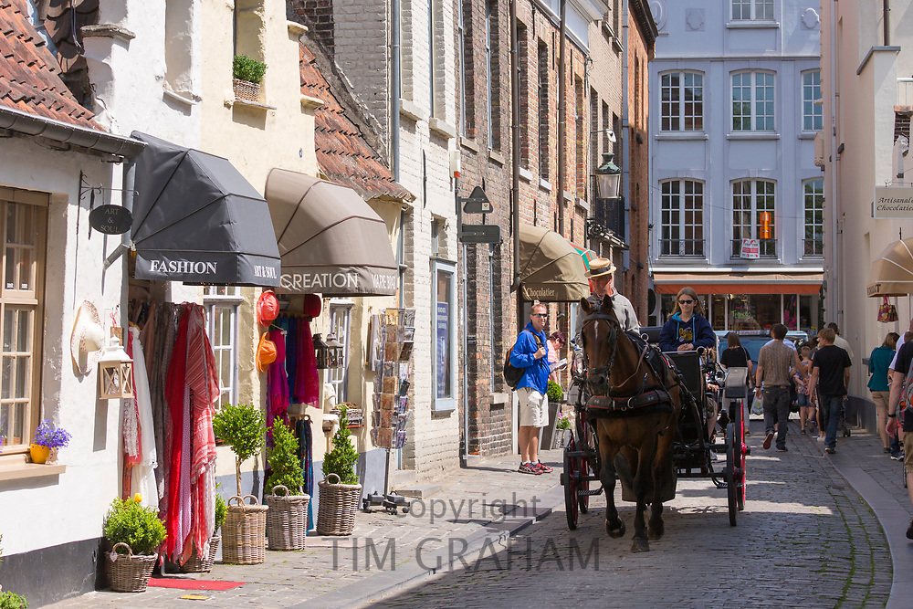 Tourists taking traditional horse and carriage sightseeing ride in Walstraat shopping street in Bruges, Belgium