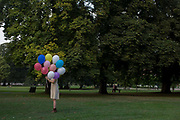 An anonymous girl stands holding a bunch of inflated balloons in Ruskin Park, a south London public space. Rising into the late-summer air, the helium-filled balloons are tied to strings and held firmly by the woman, the coloured balloons covering her face. The tall horse chestnut trees are still in leaf but about to turn brown and yellow soon in autumn and the scene is very green after recent English rain and sunshine. Londoners are in the background, enjoying the warm afternoon.