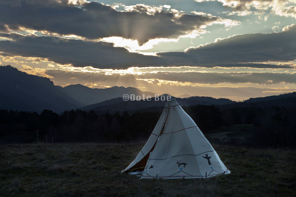 Teepee style tent with a dramatic mountain range sunset