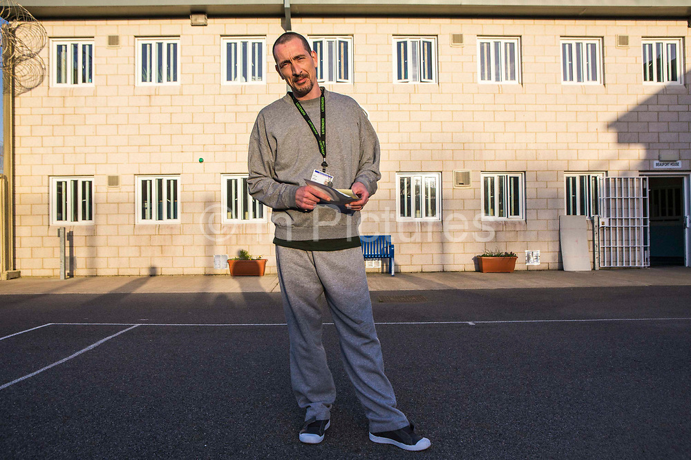 A prisoner standing in the excercise yard of the enhanced wing. HMP/YOI Portland, Dorset. A resettlement prison with a capacity for 530 prisoners. Portland, Dorset, United Kingdom.