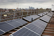 Solar photo voltaic PV panels on the roof of Elmore House, a community owned solar installation in Loughborough estate in Brixton, London, United Kingdom.  Brixton Energy Solar has installed several hundred square metres of solar panels on the roof of Elmore House in the Loughborough Estate in Brixton. Set up by Re-powering London, empower London communities to create their own renewable energy projects.