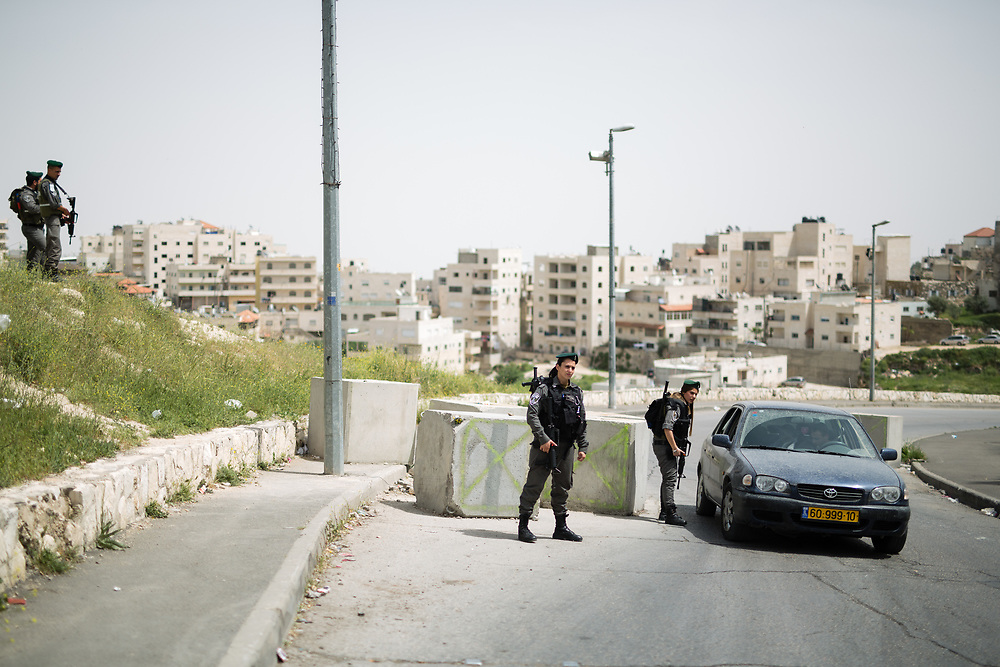 Israeli Border Police Woman Staff Sergeant Chen Cohen (R) inspects vehicles at the exit of the East Jerusalem neighborhood of Issawiya as Corporal Mor Hadad (L) and other Israeli Border Police Men stand guard, in Jerusalem, Israel, on April 10, 2016.