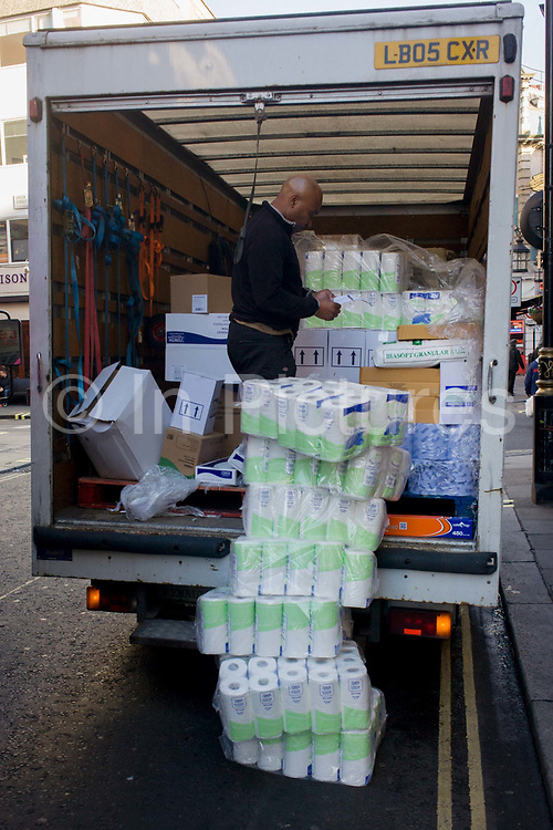 A man checks the delivery of toilet rolls from the back of a van in Soho, central London. Checking the customer's order, the driver stands in the back of his van and takes out the piles of items driven into the capital from a warehouse somewhere. Boxes are piled high and strewn around the vehicle as the transported goods make their way to various locations around the capital.