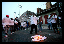 04 August 2006 - New Orleans - Louisiana. Repass after the Funeral - St Anne Street.  Friends and relatives of three young men gunned down late at night on this gritty city street on July 28th pay their respects and celebrate their lives in a repass followed by a Second line celebration, a musical tradition, march and dance led by the Rebirth Brass Band. 4 men were cruelly gunned down that night in one incident as crime spirals out of control in New Orleans. Three of the victims, all brothers buried today are Kadeem Stephen (16yrs), Kendall Stephen (21yrs) and Kareem Stephen (also 16yrs). Friends and relatives, many wearing RIP t-shirts ate, drank and gathered to remember the young victims of this heinous crime. Candles are lit and placed on an RIP t-shirt in the street in memorial to the young men at the spot they died.